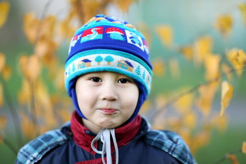 little boy in hat at fall background