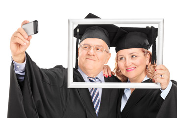 Mature couple taking a selfie behind picture frame