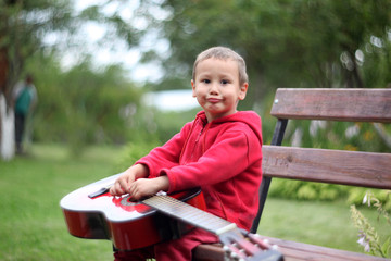 Little boy with guitar outdoors