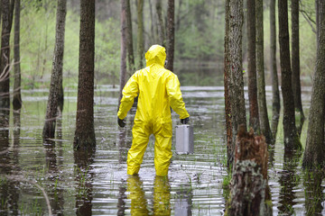 man in uniform with  suitcase  in contaminated  floods area