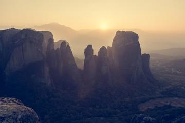 Sun setting behind sandstone rocks.