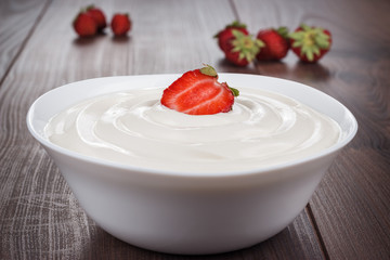 white bowl full of sour cream with strawberry