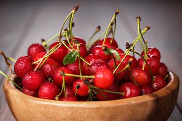 wooden bowl full of cherries on table