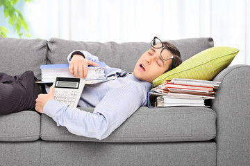 Tired employee sleeping on a sofa in an office