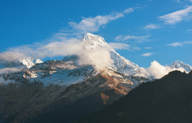 Himalayan snow mountain partly obscured by clouds