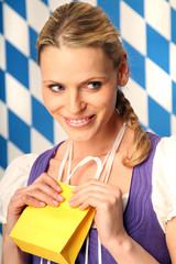 Frau im Dirndl hält Geschenktüte in der Hand