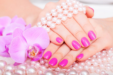 Beautiful pink manicure pedicure. Well-groomed female hands spa