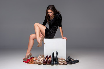 picture of sitting woman trying on high heeled shoes