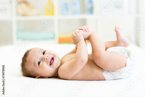 baby lying on white bed and holding legs - 74478868