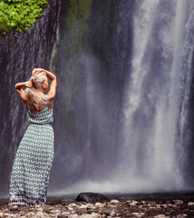young woman traveling to waterfall