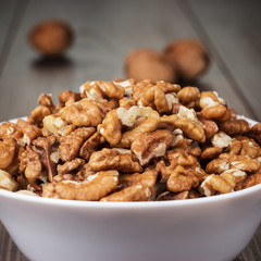 walnuts in the white bowl on wooden table