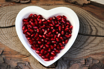 Pomegranate seeds on a plate in the form of heart
