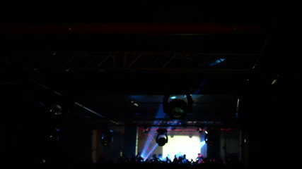crowd waving hands at concert, silhouette, stage lights