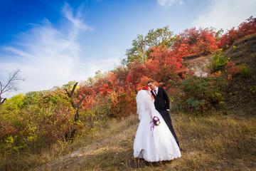 The groom, the bride, autumn park