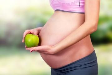 Abdomen of pregnant women and green apple.