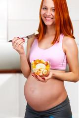 Beautiful red hair pregnant woman eating fruit salad
