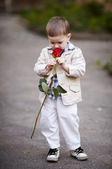 pretty boy hold red rose in hand