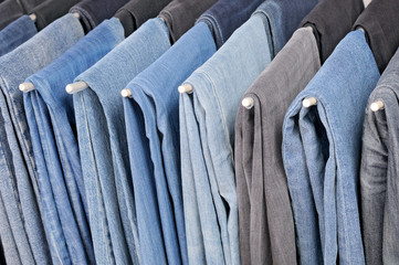 Colored jeans hanging on hangers