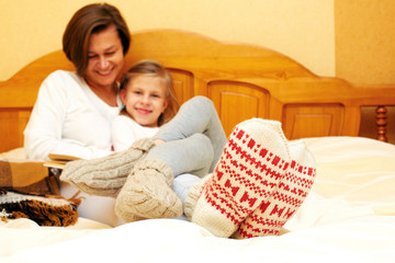 Mom and daughter lying on the bed in knitted socks