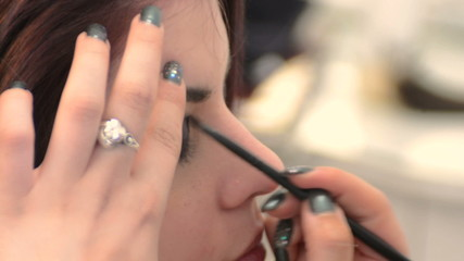Makeup artist working on fashion model's eyes