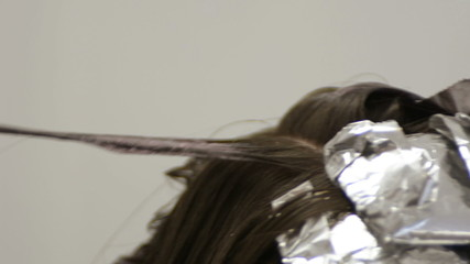 stylist dyeing hair using tin foil , close up