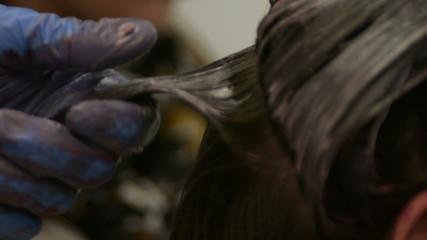 hairdresser putting dye in womans hair