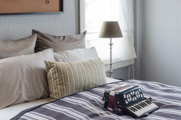 old accordion on bed in bedroom