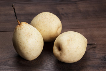 three fresh pears on wooden table