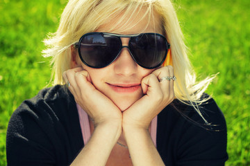young girl in sunglasses sitting on grass