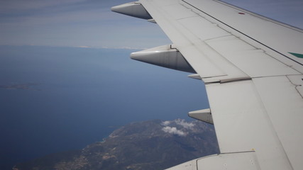 Plane flies by over the sea and the land, a view from a window