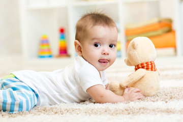 baby boy lying with plush toy