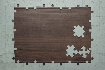 frame of puzzle pieces on wooden background