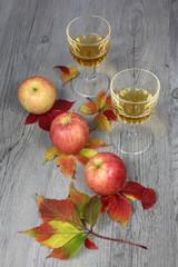 Apple juice, three apples and autumn leaves