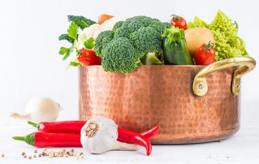 Vegetables in copper pot on white background.Vegetarian food.