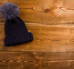 Autum , winter hat with a tassel on a wooden table