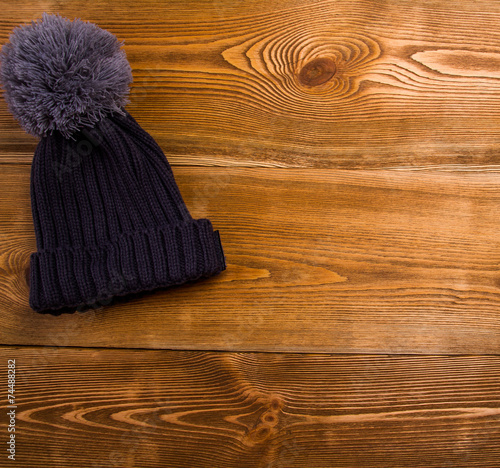 canvas print picture Autum , winter hat with a tassel on a wooden table