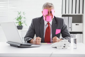 Overwhelmed businessman with sticky notes on head