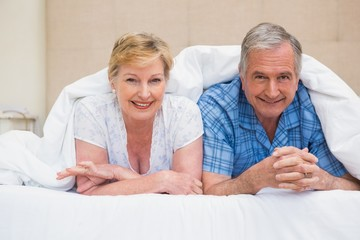 Senior couple smiling under the duvet