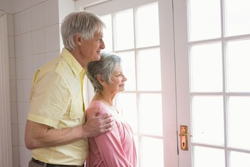 Senior couple looking out their window