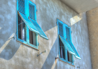 turquoise shutters in a rustic wall