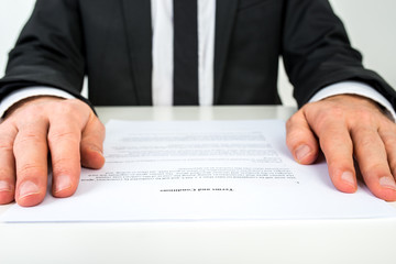 Businessman reading a document with focus to the text Terms and