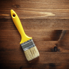 Paint brush hanging on wooden wall