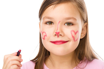 Little girl is applying lipstick on her cheek
