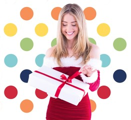Composite image of pretty santa girl opening gift