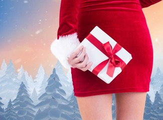 Composite image of sexy santa girl holding gift behind back