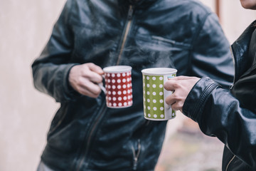 Two friends talk with two cups of hot tea in hand