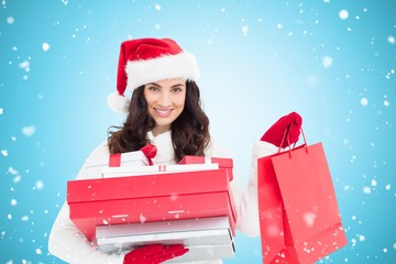 Festive brunette holding christmas gifts and bag