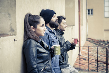 Coffee break. Three friends drinking a hot drink on the terrace