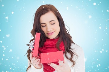 Composite image of pretty brunette opening christmas gift