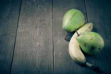 pears, bananas on an old wooden table background.tinted